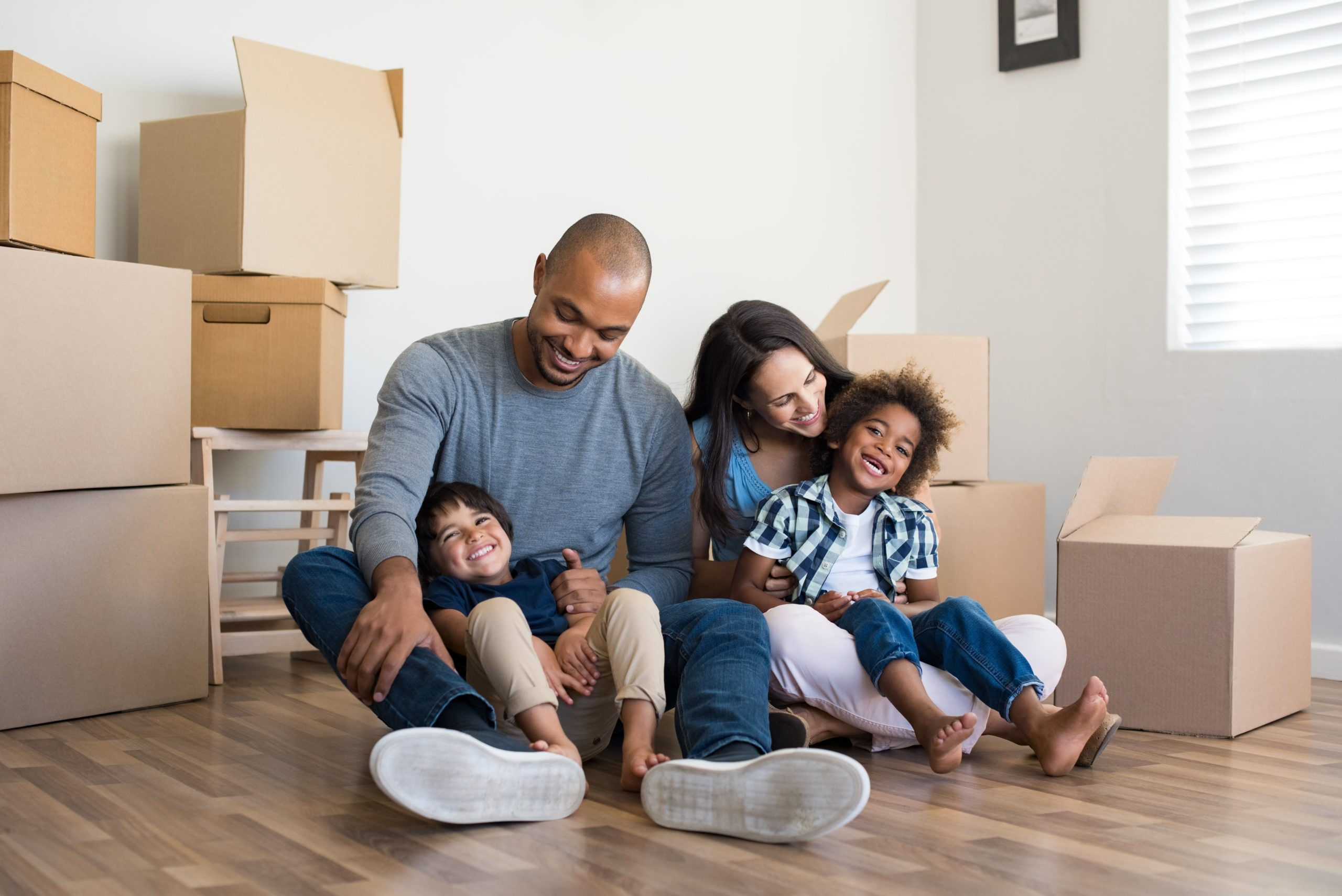 Happy family with two children having fun at new home