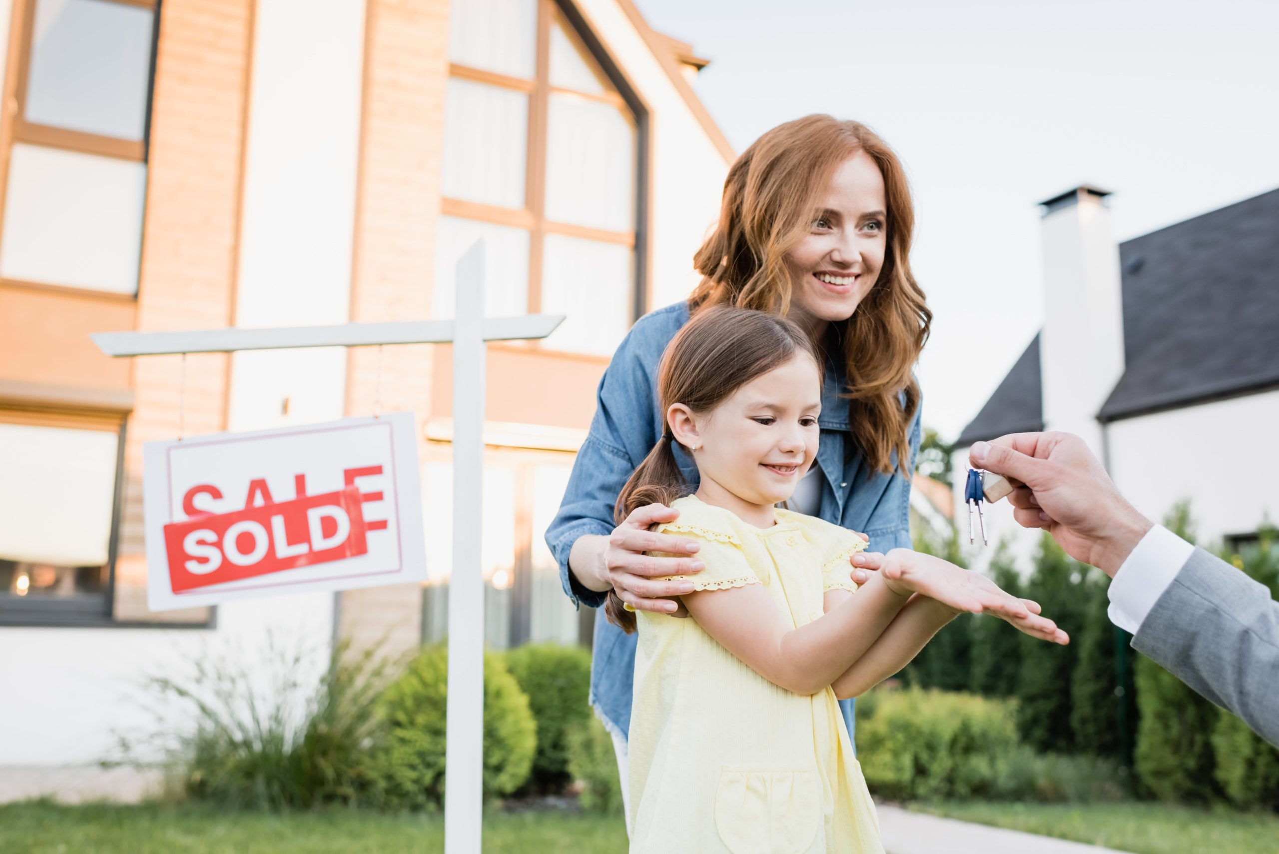 Happy mother hugging daughter taking keys from broker near sign with sold lettering on blurred background